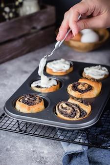 Cinnabon roll with poppy seeds on background. homemade cinnamon bun with cream cheese cream