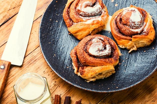 Корица с корицей и сыром маскарпоне. домашние булочки на тарелке. булочки с корицей или корицей.