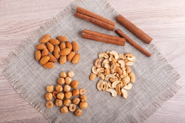 Cinnamon, almonds, hazelnuts, cashew on a linen napkin.