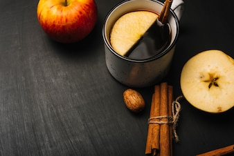 Cinnamon and kernel near drink and apples
