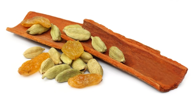 Cinnamon bark with cardamom seeds and raisin over white background
