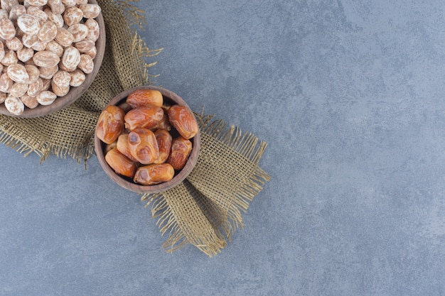 Cinnamon candies and date fruits , on the marble background.