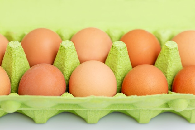 Cinnamon chicken eggs in an eco-friendly green paper container. healthy diet food. close-up. white background.