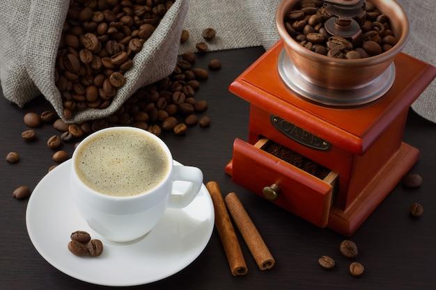 シナモン、コーヒー豆、一杯のコーヒーの周りのコーヒーグラインダー