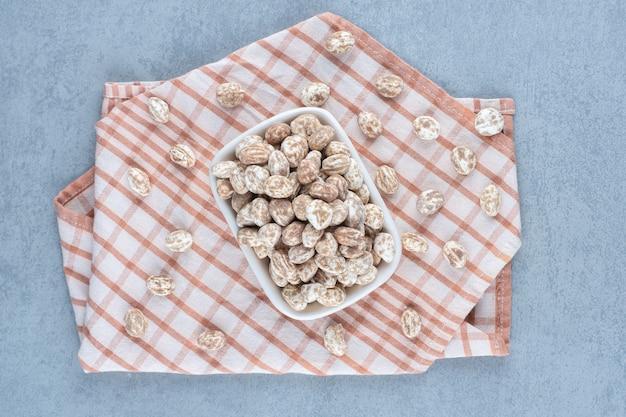 Confetteria alla cannella nella ciotola sull'asciugamano, sul tavolo di marmo.
