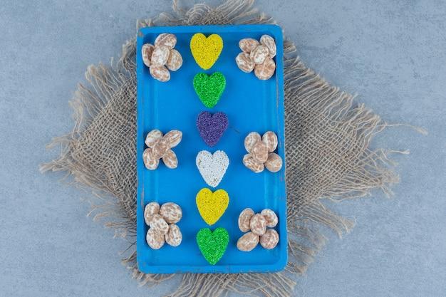 Confetteria alla cannella con biscotto sulla lavagna, sul sottopentola, sul tavolo di marmo.