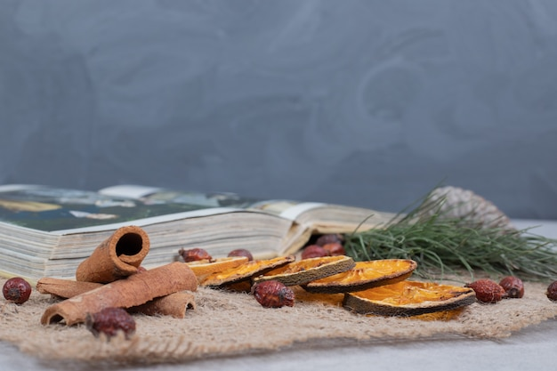Cinnamon, cranberry and dried mandarin slices on burlap. high quality photo