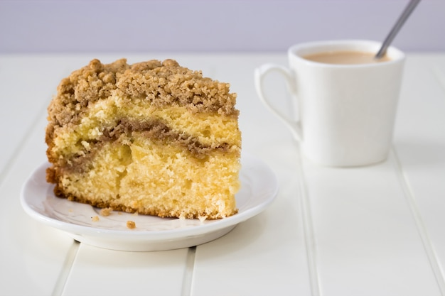 Cinnamon crumble coffee cake and cup of tea on white background