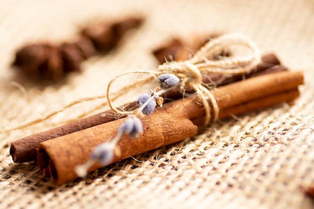 シナモンは装飾的な装飾品です。シナモンはラベンダーの花でくっつき、ジュート黄麻布にジュートロープで結ばれています。装飾。香り、香り、スパイス、調味料