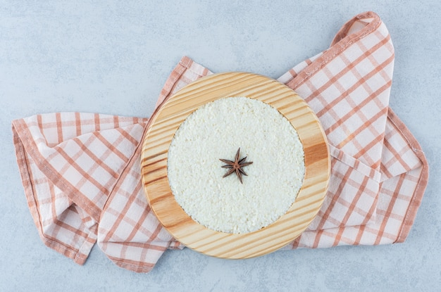 Корица на овсяной каше в деревянной тарелке на полотенце на мраморе.