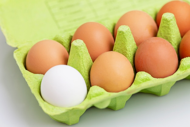 Cinnamon and one white chicken egg in an eco-green green paper container. healthy diet food. close-up. white background.