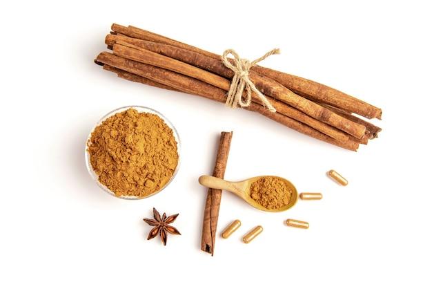 シナモンまたはカッシアの樹皮、粉末、カプセルを白で分離