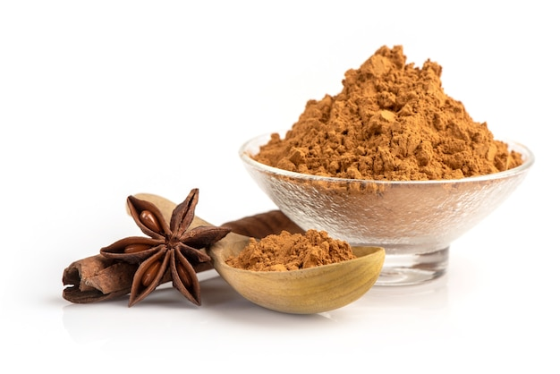 白に分離されたシナモンまたはカッシアの樹皮、粉末および油。