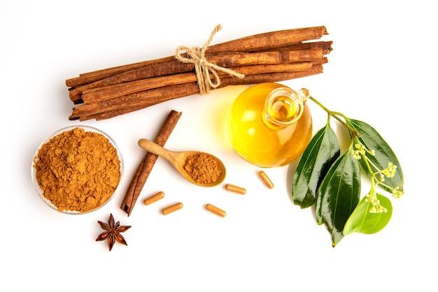 シナモンまたはカッシアの樹皮、粉末、カプセル、花、緑の葉、白で分離されたオイル