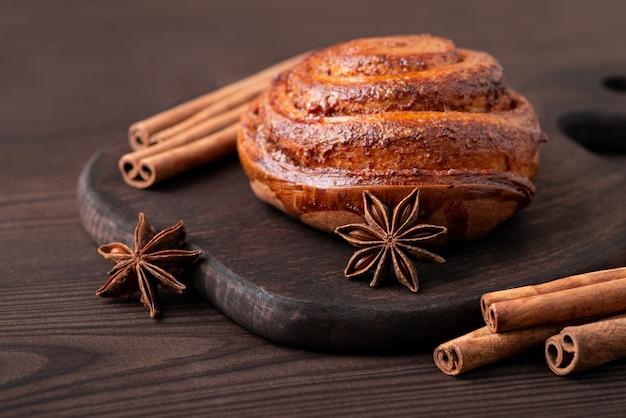 Булочка с корицей на коричневой разделочной доске с звездочкой аниса и палочками корицы вокруг нее