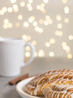 シナモンロールまたはシナモンパンのデザートと白い一杯のコーヒークラシックなアメリカまたはフランスのパン屋のボケ味