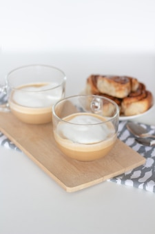 Булочки с корицей и чашка кофе на белом фоне