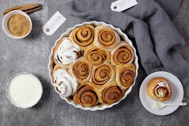 Булочки с корицей, булочки, корица в форме для запекания с коричневым сахаром, сливочно-сырным соусом.