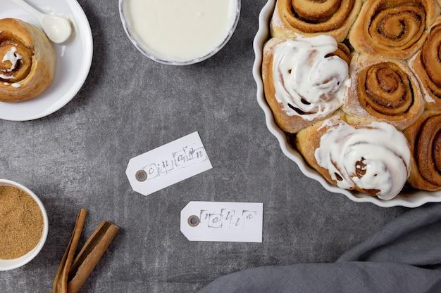 Булочки с корицей, булочки в форме для запекания с коричневым сахаром, творожно-сливочным соусом и палочками корицы.