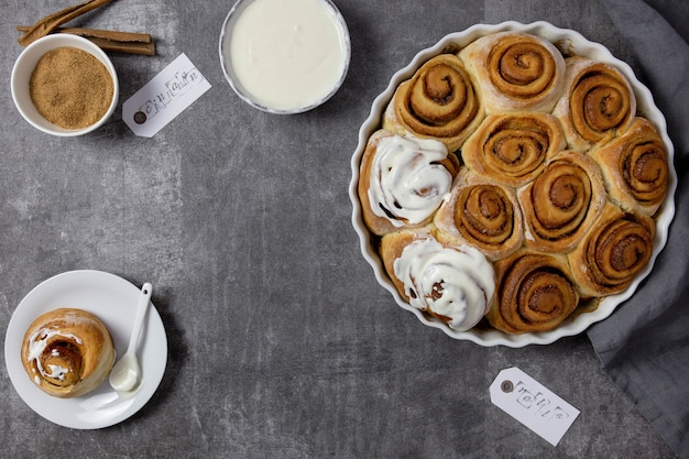 Cinnamon rolls, cinnabon buns in a baking dish with brown sugar, curd cottage cheese cream fondant sauce and cinnamon sticks on dark gray surface