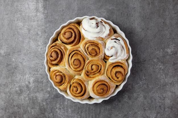 Cinnamon rolls, cinnabon buns in a baking dish with curd cottage cheese cream fondant sauce on dark gray surface