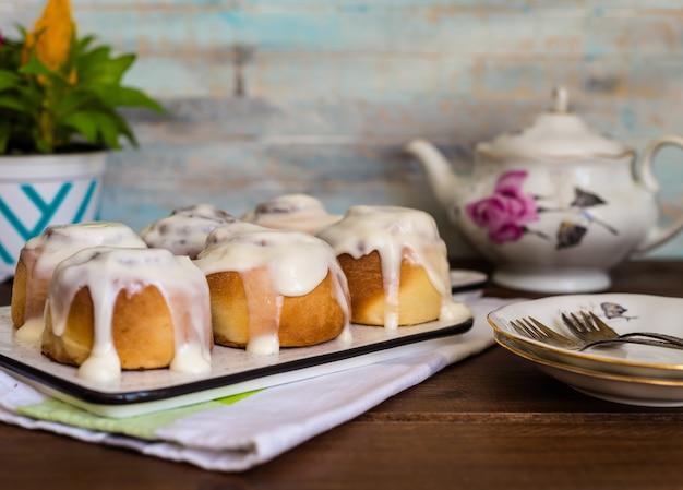 Булочки с корицей или циннабон, домашние сладкие традиционные десертные булочки с белым сливочным соусом