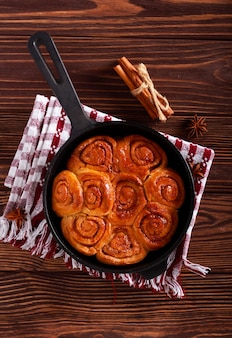 Cinnamon rolls in a skillet pan over wooden table