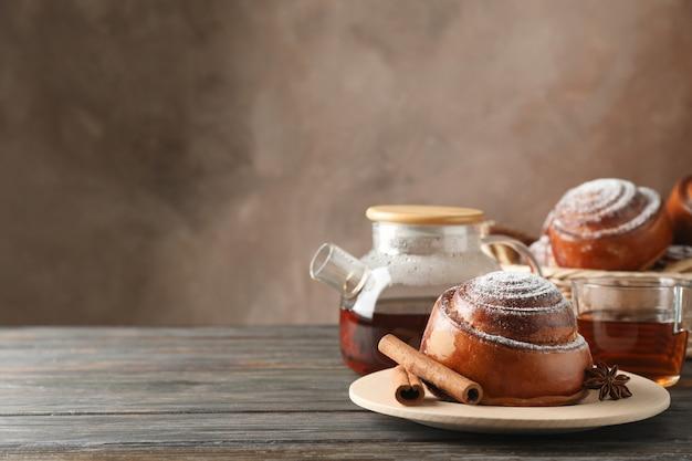 Cinnamon rolls, tea and wicker basket on wooden table