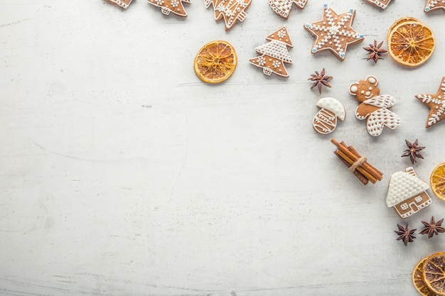Cinnamon star anise gingerbread and dry orange on white concrete background. top of view.
