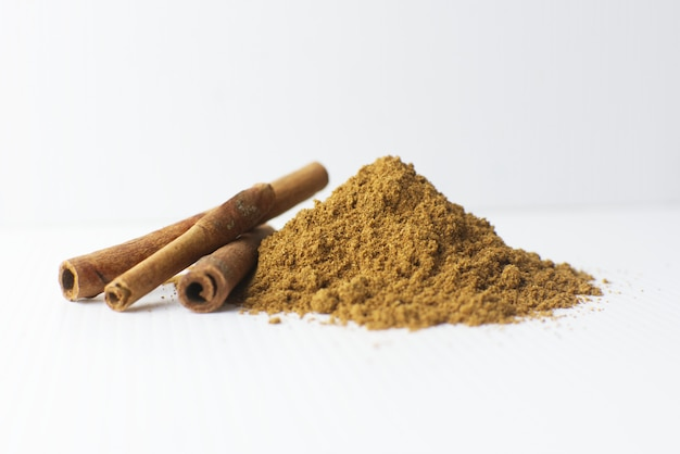 Cinnamon stick and cinnamon powder on white background