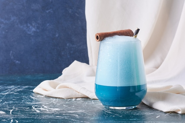 Cinnamon stick with a cup of drink on blue.