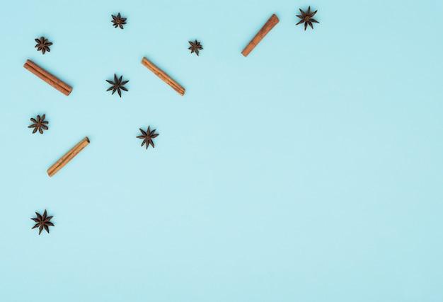 Палочки корицы и звезды аниса на синем фоне. плоский стиль