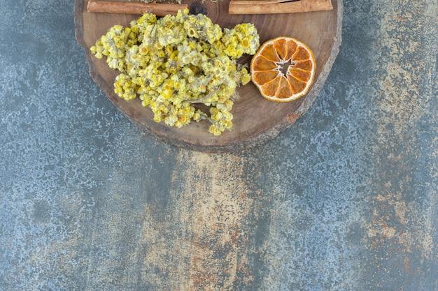Палочки корицы и хризантемы на деревянной доске.