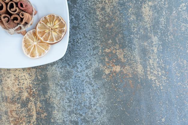 Палочки корицы и нарезанные лимоны на белой тарелке.