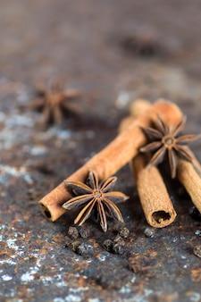 Cinnamon sticks, anise stars and black peppercorns on textured background