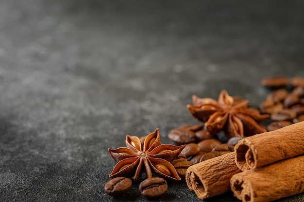 Cinnamon sticks, anise stars and coffee beans on dark grey background. copy space, close up