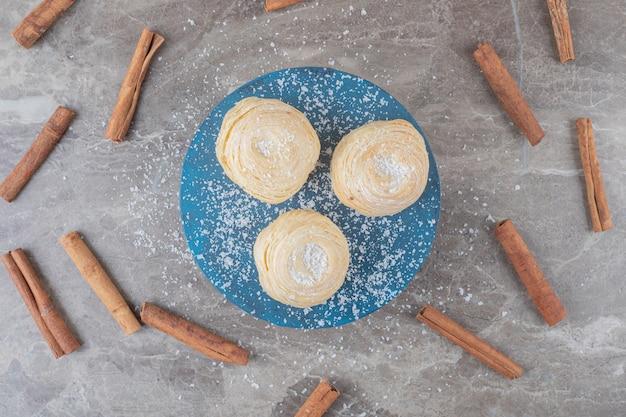 シナモンは大理石の表面のボード上の薄片状のクッキーの周りにくっつきます