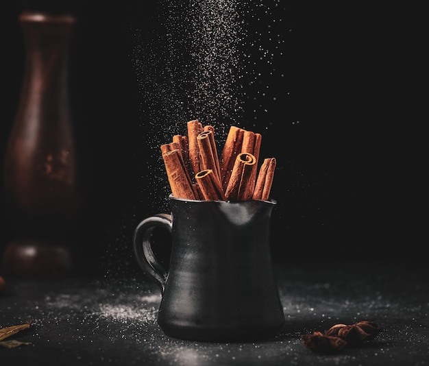 Cinnamon sticks in black cup