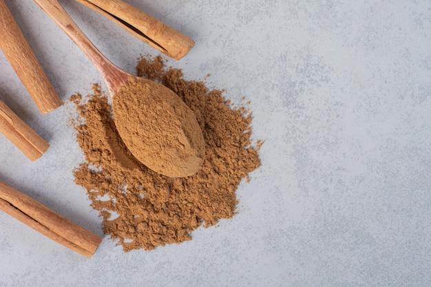 Bastoncini di cannella e polvere frullata in un cucchiaio di legno.
