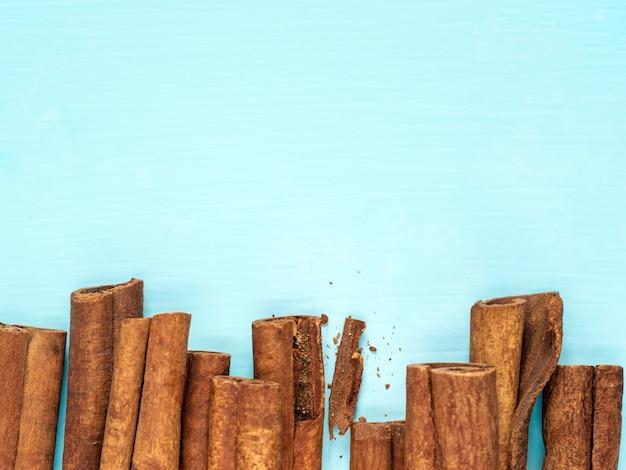 Cinnamon sticks on blue with copy space
