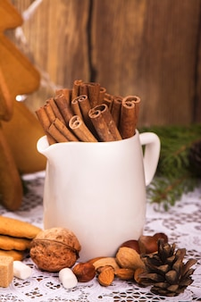 Cinnamon sticks, brown sugar and assortment of nuts over wooden rustic background. toned image