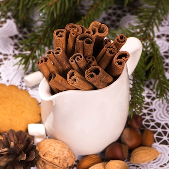 Cinnamon sticks, brown sugar and assortment of nuts over wooden rustic background.