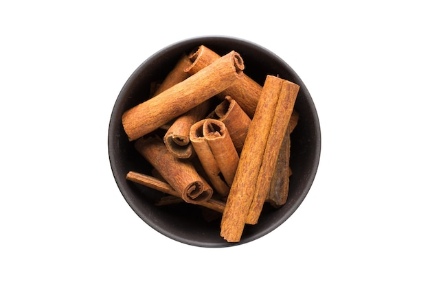 Cinnamon sticks in clay bowl isolated on white background. seasoning or spice top view