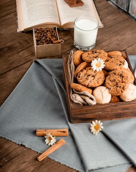 Cinnamon sticks and a cookie box on a blue tablecloth