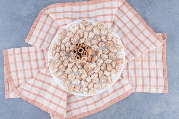 Bastoncini di cannella e biscotti sull'asciugamano, sullo sfondo di marmo.
