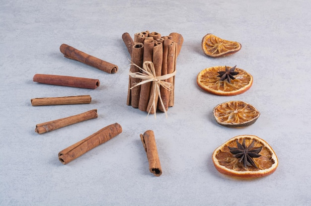 Cinnamon sticks, dry orange slices and anise flowers on concrete surface.