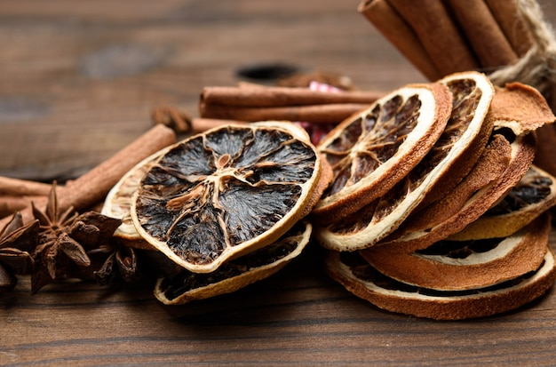 Cinnamon sticks and dry orange slices on brown wooden board, close up