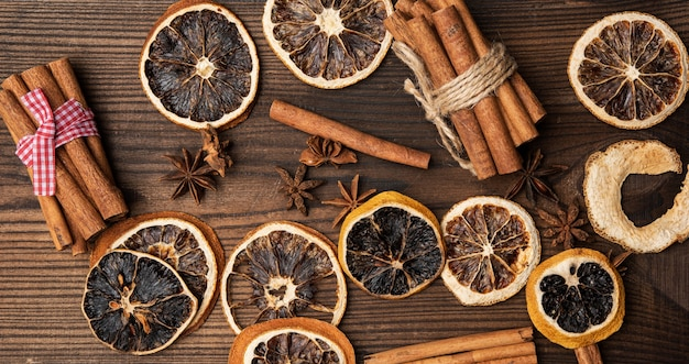 Cinnamon sticks and dry orange slices on brown wooden board, top view