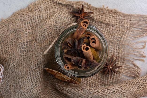 Bastoncini di cannella in barattolo di vetro con tela. foto di alta qualità
