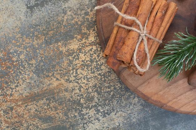 Палочки корицы в веревке на мраморном фоне. фото высокого качества